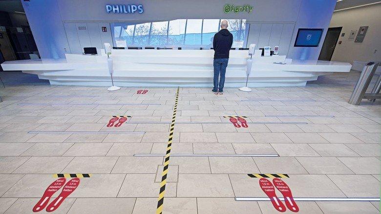 Distanz: Markierungen auf dem Boden sorgen am Philips-Empfang für den nötigen Abstand.