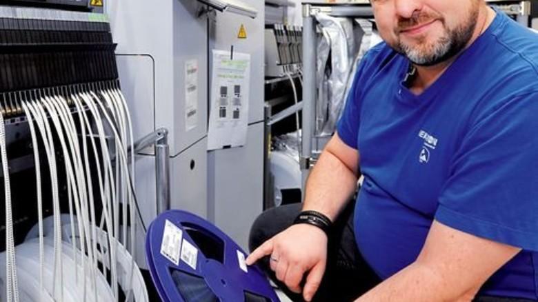 Stolz auf seinen Job: Tino Schönfeld kontrolliert eine Rolle mit Bauelementen für Leiterplatten. Foto: Sigwart