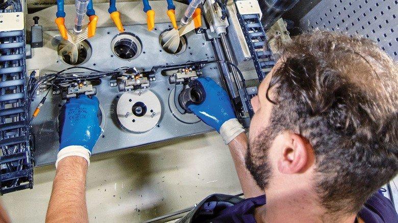 Fertigung: Fabian Schmitz an einer Maschine, in der Räumwerkzeuge eingesetzt werden.