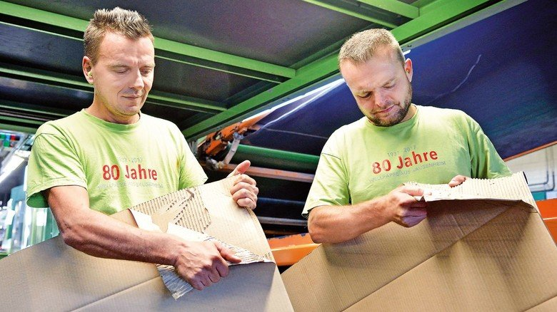 Qualitätskontrolle: Maschinenführer Ekrem Rama (links) und Anlagenführer Jan Bickel prüfen die Verklebung der noch warmen Wellpappebögen.