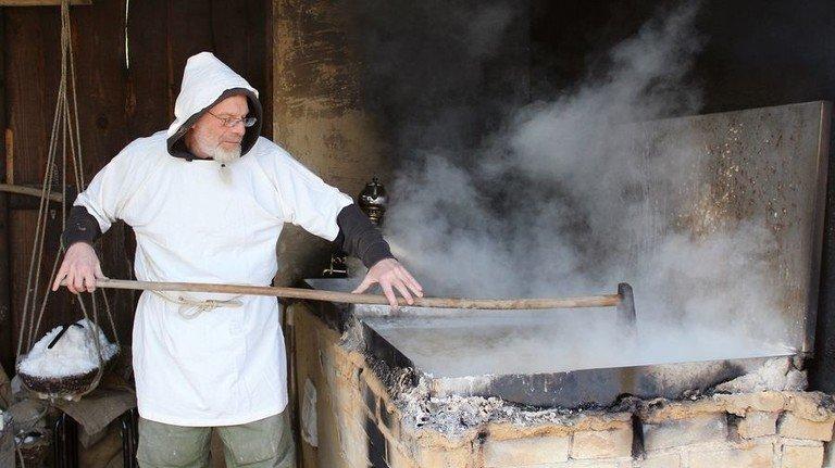Knochenjob: Ein Museumsmitarbeiter zeigt, wie früher Salz gesiedet wurde. Foto: Deutsches Salzmuseum