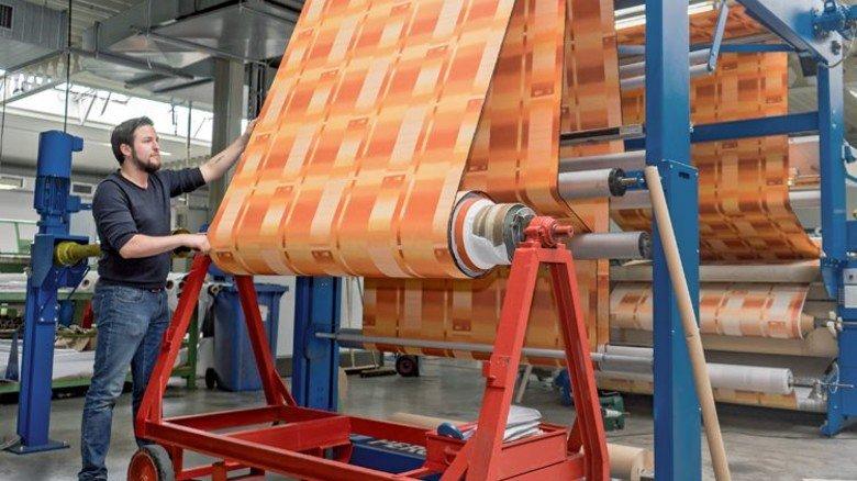 Rollenweise Muster: Textilveredler Daniel Neumann mit einem Dekostoff. Foto: Egbert