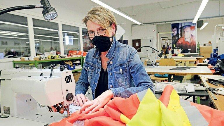 Blick in den Nähsaal: Martina Alfes vernäht den orange-gelb leuchtenden Oberstoff einer Jacke.