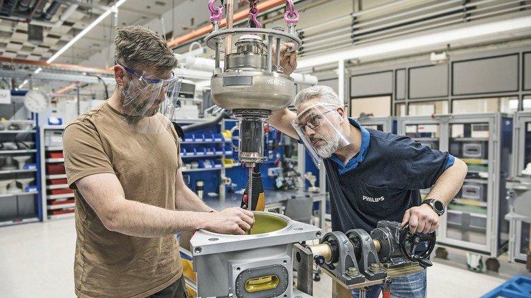 Passgenau: Die Monteure Andreas Hinz (links) und Hicham Al Mellouki setzen eine Röntgenröhre in  ein CT-Modul.