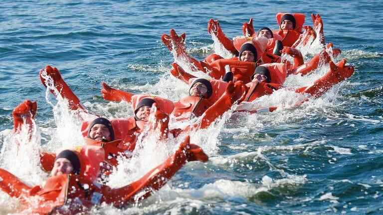 Überlebenstraining: Teilnehmer einer Offshore-Übung im Wasser des Rostocker Hafens.