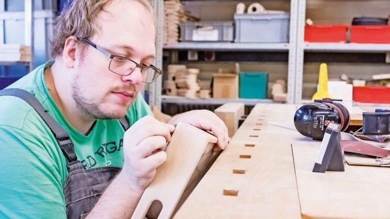 Fokussiert: Markus Peinemann schleift die Ecken eines Holztabletts. Foto: Heidrich