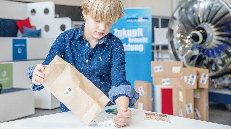 Was ist wohl drin im Bastelpaket? Henri schüttet den Inhalt der großen Tüte auf einen Tisch. Das spannende Tüfteln beginnt.