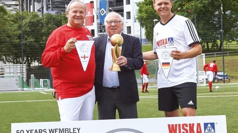 Wimpeltausch: Wiska-Geschäftsführer Ronald Hoppmann (rechts) mit seinem englischen Kollegen Will Rich (links) und Uwe Seeler. Foto: Werk