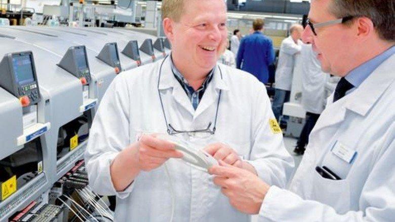 Smarte Fabrik: Produktionstechniker Uwe Ratte (links) und Geschäftsführer Gerd Ohl vor der sich selbst steuernden Anlage. Foto: Scheffler
