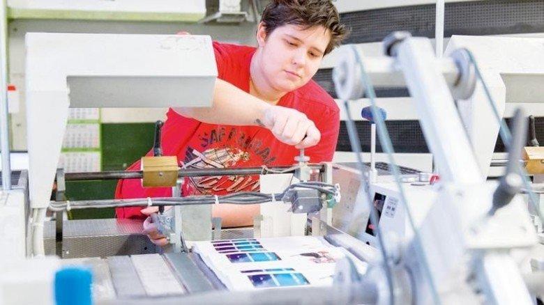 Justierung: Azubi Ann-Christine Gerritzen stellt eine Bindemaschine ein. Foto: Straßmeier