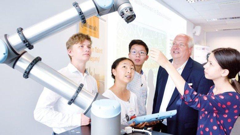 Anfassen erlaubt: Wolfgang Michel, Ausbilder bei Continental in Babenhausen, erklärt den Siegern des Hessischen Mathematik-Wettbewerbs einen kollaborativen Roboter. Foto: Scheffler