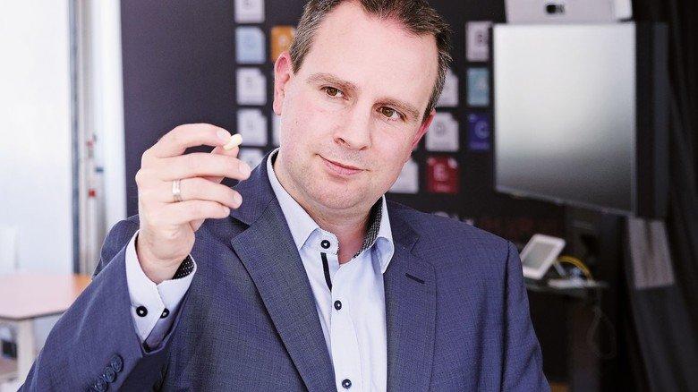 Herausforderung: Henning Kleine zeigt eine große Tablette, die vom feinen Wirkstoffpulver im Röhrchen ersetzt würde.