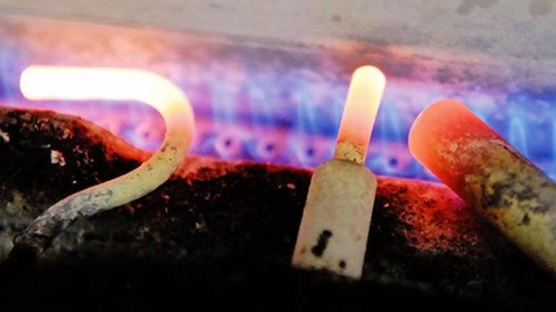 Der Trick mit dem Feuer: Rasant sausen die künftigen Faltschachteln (grau) an der Flammenleiste vorbei. Foto: Scheffler