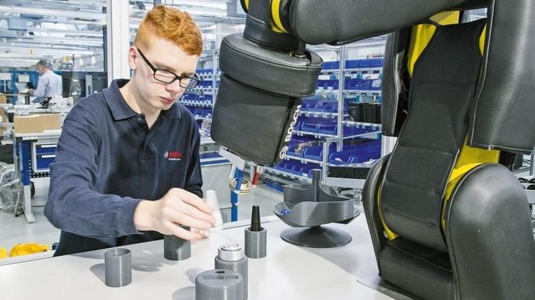 Hand in Hand mit dem Roboter: Jean-Pierre Ullrich führt eine moderne Montage-Station vor. Foto: Mierendorf