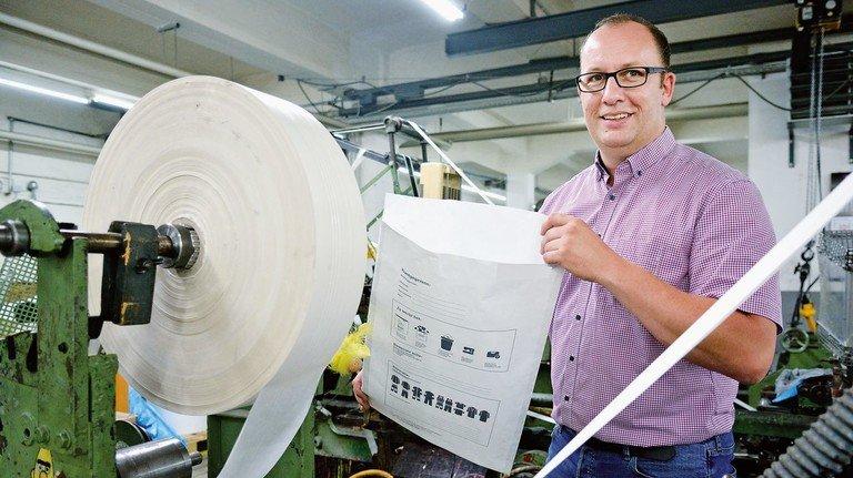 Er wagte den Wechsel vom Angestellten zum Unternehmer: Jens Vonderheid, hier mit einer Papiertüte für Berufskleidung.