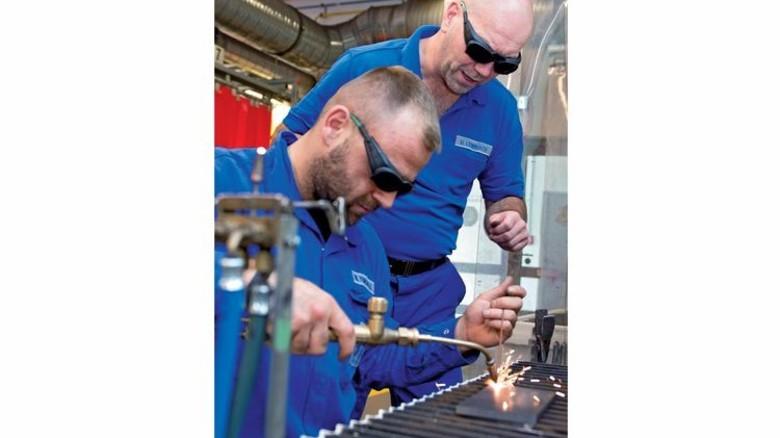 Im Job: Ausbilder Uwe Leimbach (rechs) mit seinem Kollegen Macit Tuncaelli. Foto: Moll