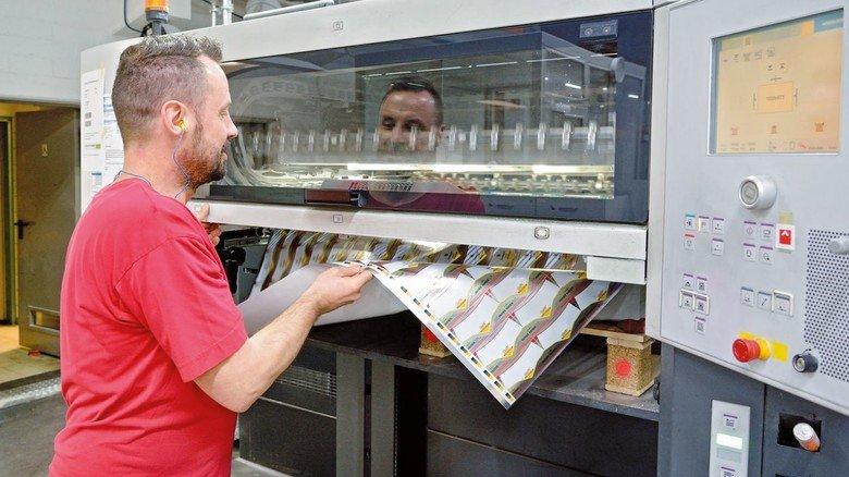 Know-how: Martin Stolch nimmt einen Druckbogen aus der Maschine, zur Qualitätskontrolle.