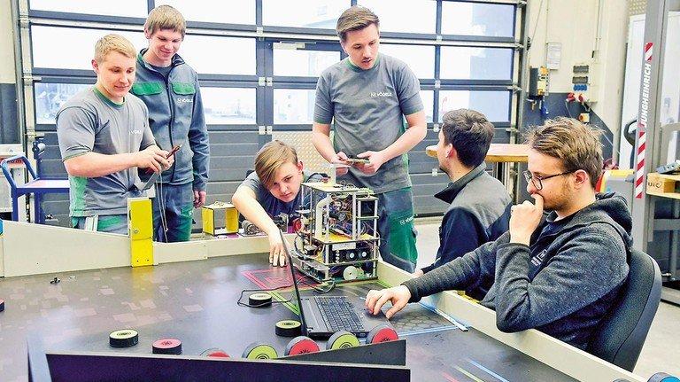 """Knifflig: Der Roboter """"Nr. 5"""" steht da wie ein Klotz. Wie bringt man ihn dazu, bestimmte Aufgaben selbständig zu erledigen? Daran tüfteln die Vögele-Azubis. Foto: Sandro"""