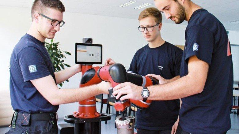 """Robotik: Auszubildende von ZF Passau üben den Umgang mit dem automatisierten """"Kollegen"""". Foto: Werk"""