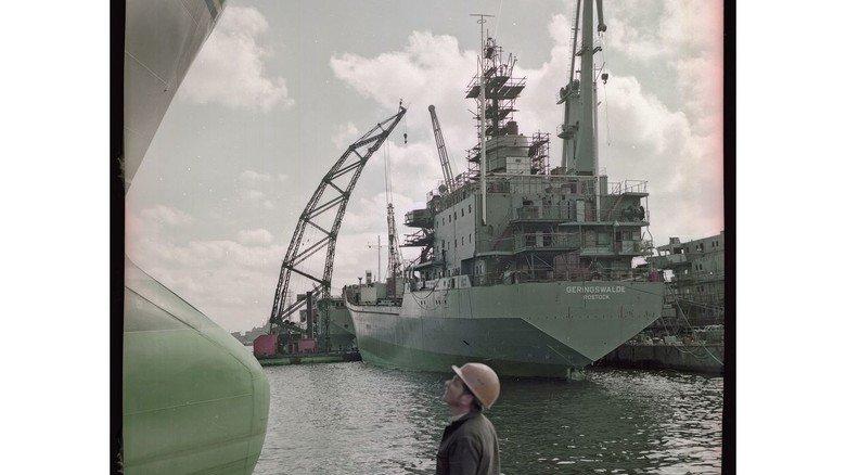 """Ausrüstungskai: Zu den auf der Neptun Werft für die Deutsche Seereederei (DSR) gebauten Schiffen gehörte auch eine Serie von Stückgutfrachtern des Typs Poseidon. Diese Aufnahme aus dem Jahr 1977 zeigt die """"MS Geringswalde""""."""