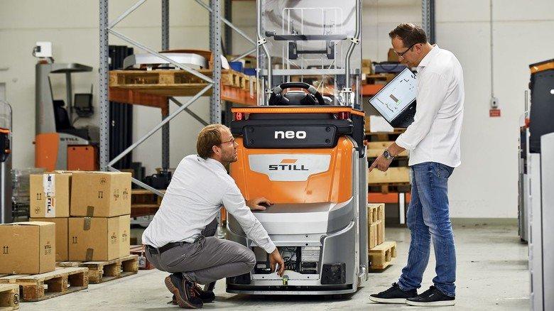 Kreative Entwickler: Volker Viereck (rechts) und sein Kollege Tino Krüger-Basjmeleh an dem Flurförderzeug, das mit künstlicher Intelligenz ausgestattet wurde.