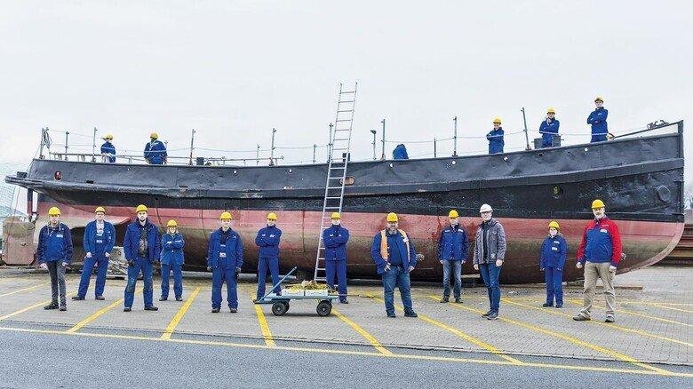 """Gruppenbild mit Dampfschiff: Die beteiligten Azubis mit ihren Ausbildern vor der """"Dortmund IX"""", die Anfang 2021 nach Papenburg gebracht wurde, um dort künftig als Museumsschiff zu dienen."""