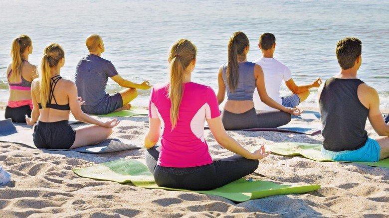 Yoga am Strand: Gut möglich, dass hier die Teilnehmer einer Gesundheitsreise ganz in sich versunken sind.