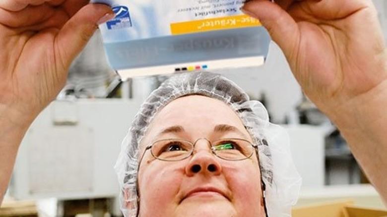 Produktion: Mitarbeiterin Ute Neumann kontrolliert eine Faltschachtel für Fischfilet. Foto: Scheffler