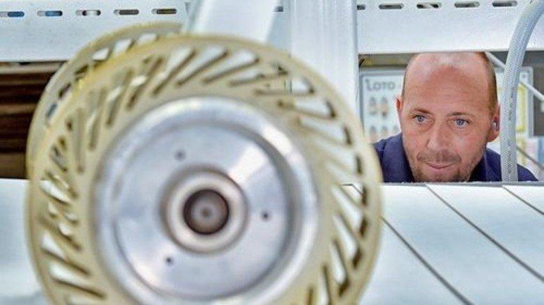 Produktion: Maik Perlik schaut am Übergang vom Drucker zur Stanze nach dem Rechten. Foto: Deutsch
