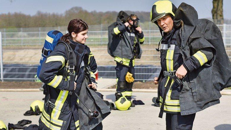 Gut gerüstet: Feuerwehrfrau Cecilia Meier mit einem Kollegen in voller Schutzausrüstung.