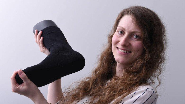 Made with Kohlendioxid: Ricarda Wissel mit einer Socke, in der das spezielle Garn verstrickt ist.