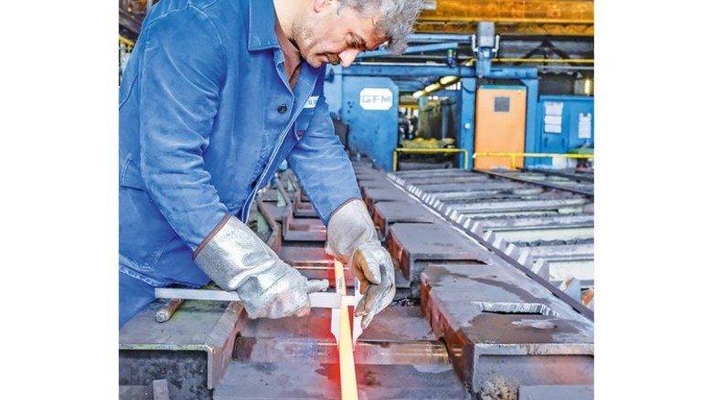 Präzision: Ünal Öner vermisst den gewalzten Knüppel mit der Hand – beim glühenden Stahl liefert das genauere Ergebnisse als die moderne Messtechnik. Foto: Roth