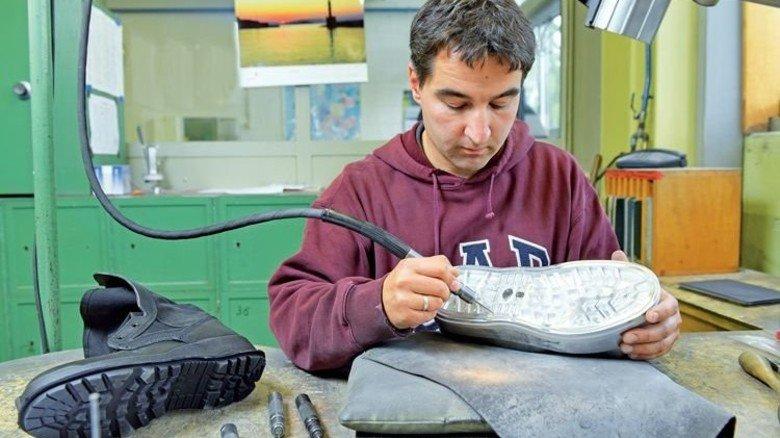 Letzter Schliff: Graveur Ronald Jakobeit arbeitet an einem Bodenstempel, welcher der Sohle später ihr Profil gibt. Foto: Augustin