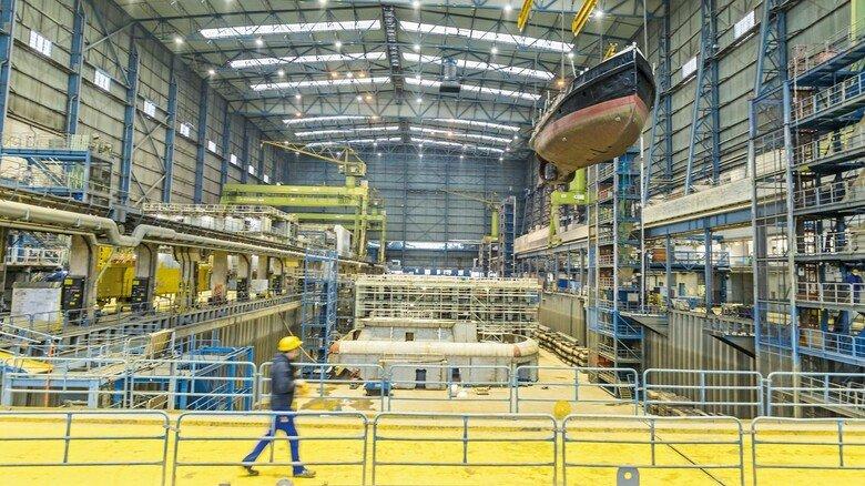 """Unter dem Dach: In der Halle 5, in der die """"Dortmund IX"""" hier am Kran hängt, wirkt das Schiff wie eine Nussschale. Kein Wunder, das Gebäude ist 60 Meter hoch, 370 Meter lang und rund 100 Meter breit."""