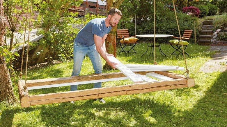 Lieblingsplatz: Der selbst gebaute Bettrahmen mit Lattenrost wird an einem dicken Ast aufgehängt.