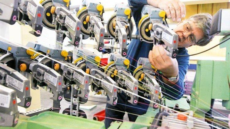 Buntes Garn: Webtechniker Luis Friedlmeier kontrolliert die Spulen. Foto: Puchner
