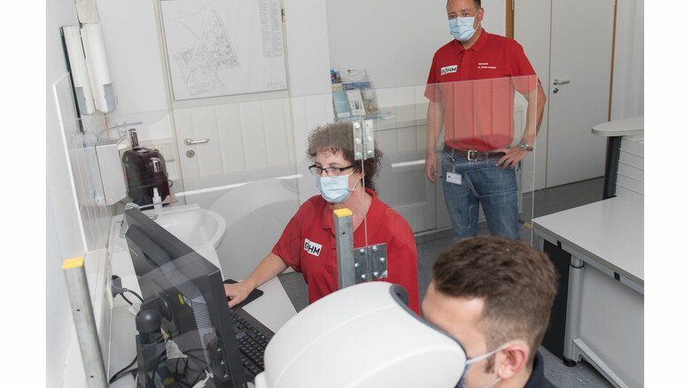 Alles sicher: Trennscheiben aus Plexiglas schützen jetzt die Teilnehmer einer routinemäßigen Augenuntersuchung im Werk.