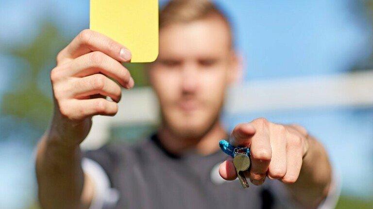 Gelbe Karte: Die gibt es oft genug beim Fußball. Im Job übernimmt ihre Funktion die Abmahnung. Foto: Adobe Stock