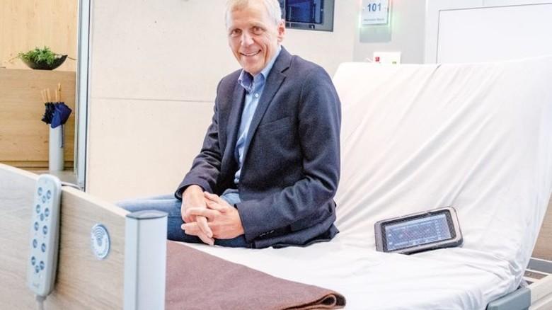 Der Firmenchef: Meinolf Köhn auf dem Hightech-Bett, das mit dem Tablet vernetzt ist – und im Notfall den Pfleger ruft. Foto: Roth