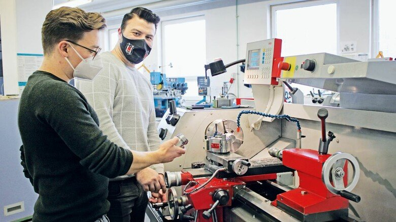Viel Praxis: Hüseyin Özkoc (rechts) mit einem seiner Ausbilder an der Drehmaschine.