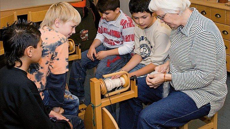 An einigen Ausstellungsstücken, etwa am Krempel und Handspinnrad, können Kinder unter Anleitung selbst Hand anlegen. Foto: Nordwolle Mueseum