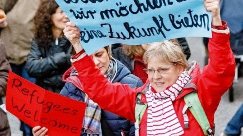 Willkommen: Eine Hamburgerin begrüßt ankommende Flüchtlinge. Foto: dpa