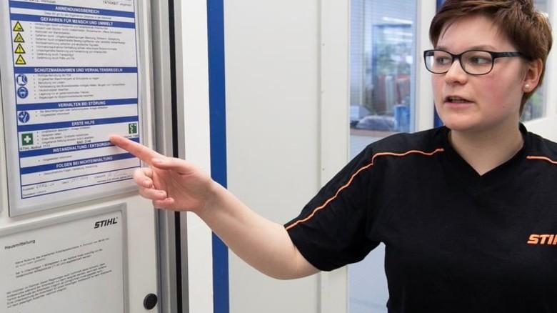Junior-Sicherheitspartnerin Ramona Stark erklärt eine Betriebsanweisung für den Werkstattbereich im Ausbildungscenter. Foto: Mierendorf