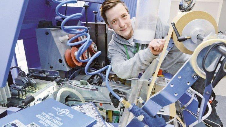 Wartung: Michaela Reiter an einer Maschine, die den Buchblock und die Buchdecke zusammenbringt. Foto: Sturm