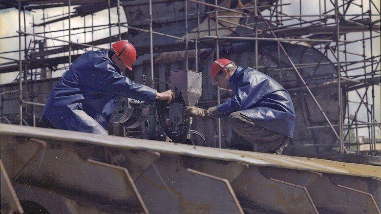 Stahlbau: Auf der Helling der Neptun Werft im Jahr 1970. Zwei Schiffbauer sind mit Stahlarbeiten an einem neuen Schiff beschäftigt.