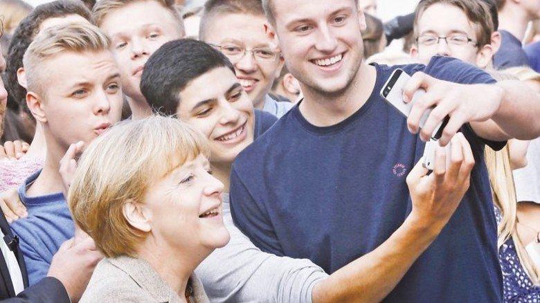 Lächeln fürs Selfie: Smart möchte Kanzlerin Angela Merkel rüberkommen. Foto: dpa