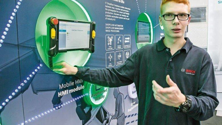 Wissen weitergeben: Der Azubi erläutert das Prinzip der vernetzten Fertigung. Foto: Mierendorf