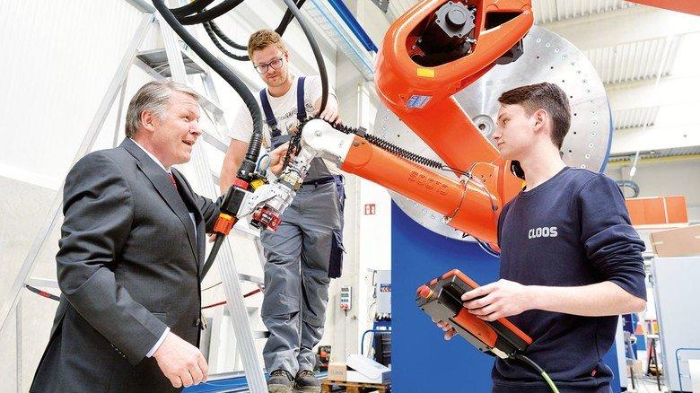 An einer Anlage für Baumaschinen: Sieghard Thomas (CEO) Azubi David Heuser und Roboterprogrammierer Tim Brachthäuser