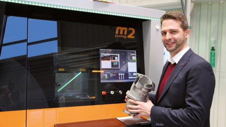 Faszination 3-D-Druck: Eike Tholema mit einem Rohrkrümmer, der Schicht für Schicht aus Titanpulver aufgebaut wurde. Foto: GUS