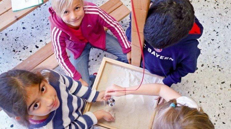 Wie schwingt ein Pendel? Doga und Matilda lassen es Kurven im Sand zeichnen. Foto: Higo